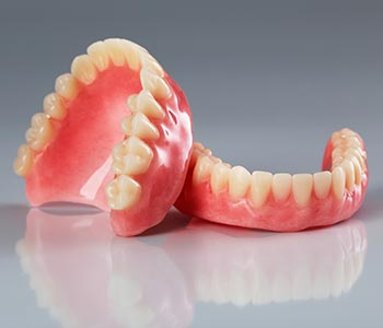 Dentures Waterloo ON holding best denture set in hands